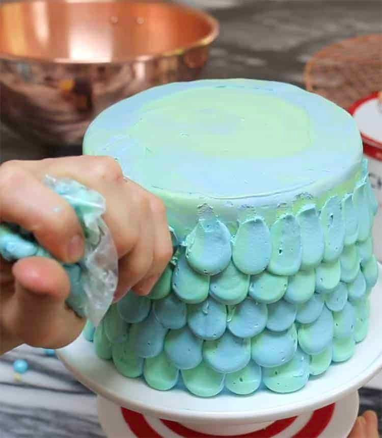 a mermaid cake being piped with light blue buttercream