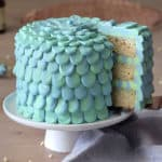A three layer bluegreen cake on a white cake stand