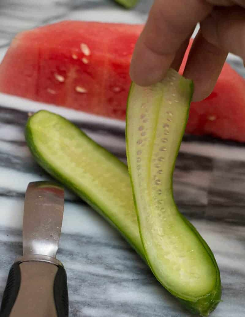 A photo of a cucumber being peeled.