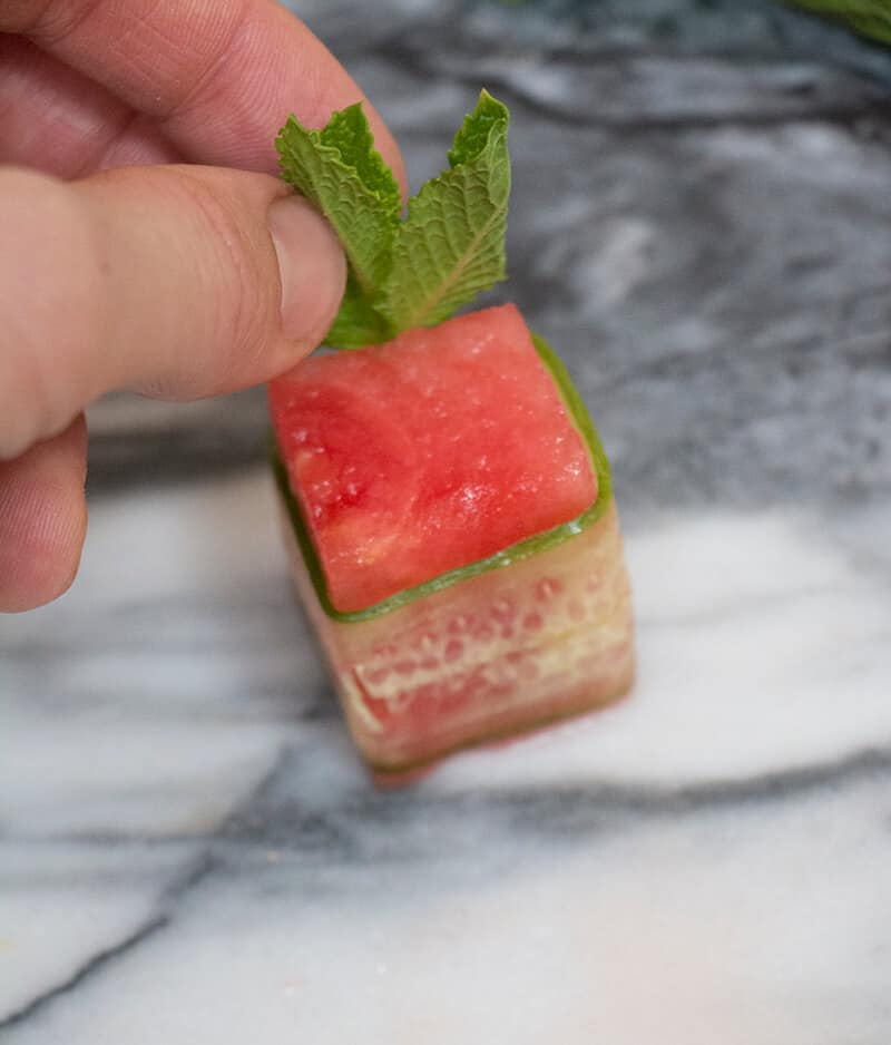 A process shot of a watermelon canapé being made.