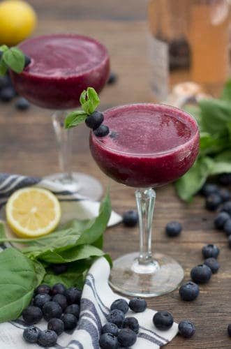 A photo of a Frosé cocktail in a glass garnished with blueberries and basil.