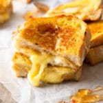 A photo of a freshly made grilled cheese cut in half with melted cheese oozing out.