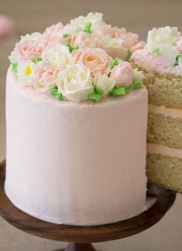 A photo of a cake with buttercream roses on top.