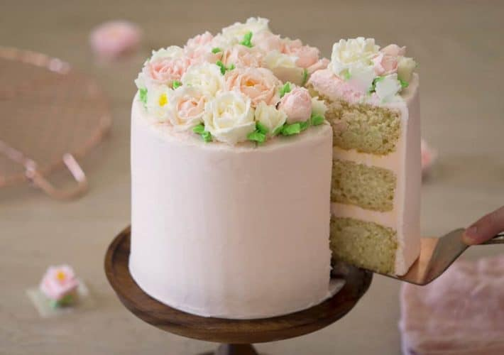 A photo of a cake decorated with vanilla buttercream flowers.