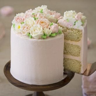 a photo of a cake covered in buttercream roses