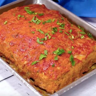 A photo of turkey meatloaf fresh out of the oven and garnished with parsley.