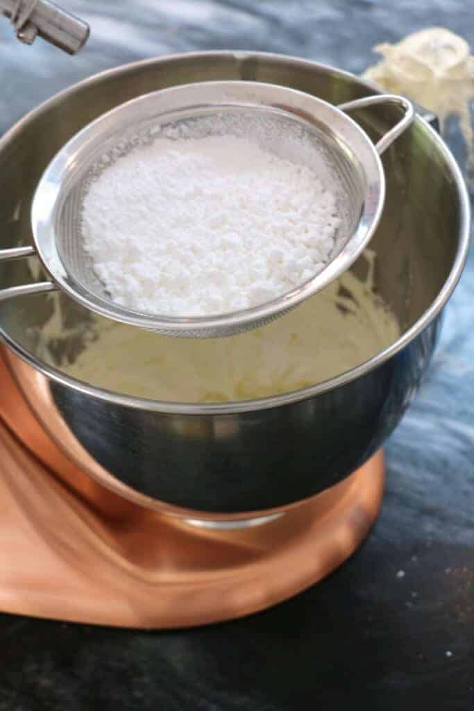 A photo of confectioners sugar being sifted into a stand mixer.