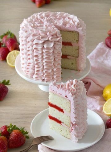 A photo of a pink Strawberry Lemonade Cake with a piece being removed