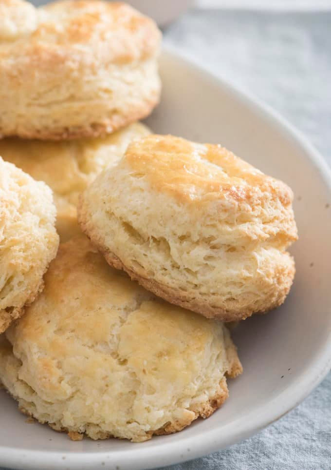 A photo of a soft pink plate holding fluffy buttermilk biscuits.