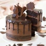 A chocolate zucchini cake with a ganache drip on a cake stand