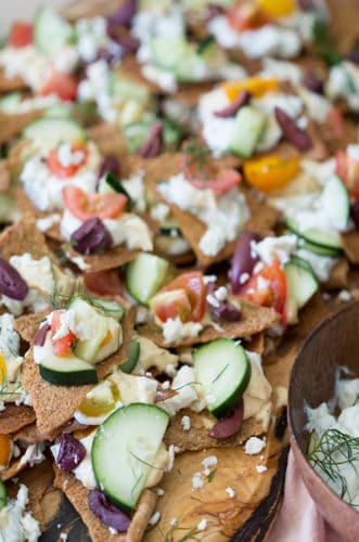A photo of Greek Nachos with tomatoes and cucumbers.