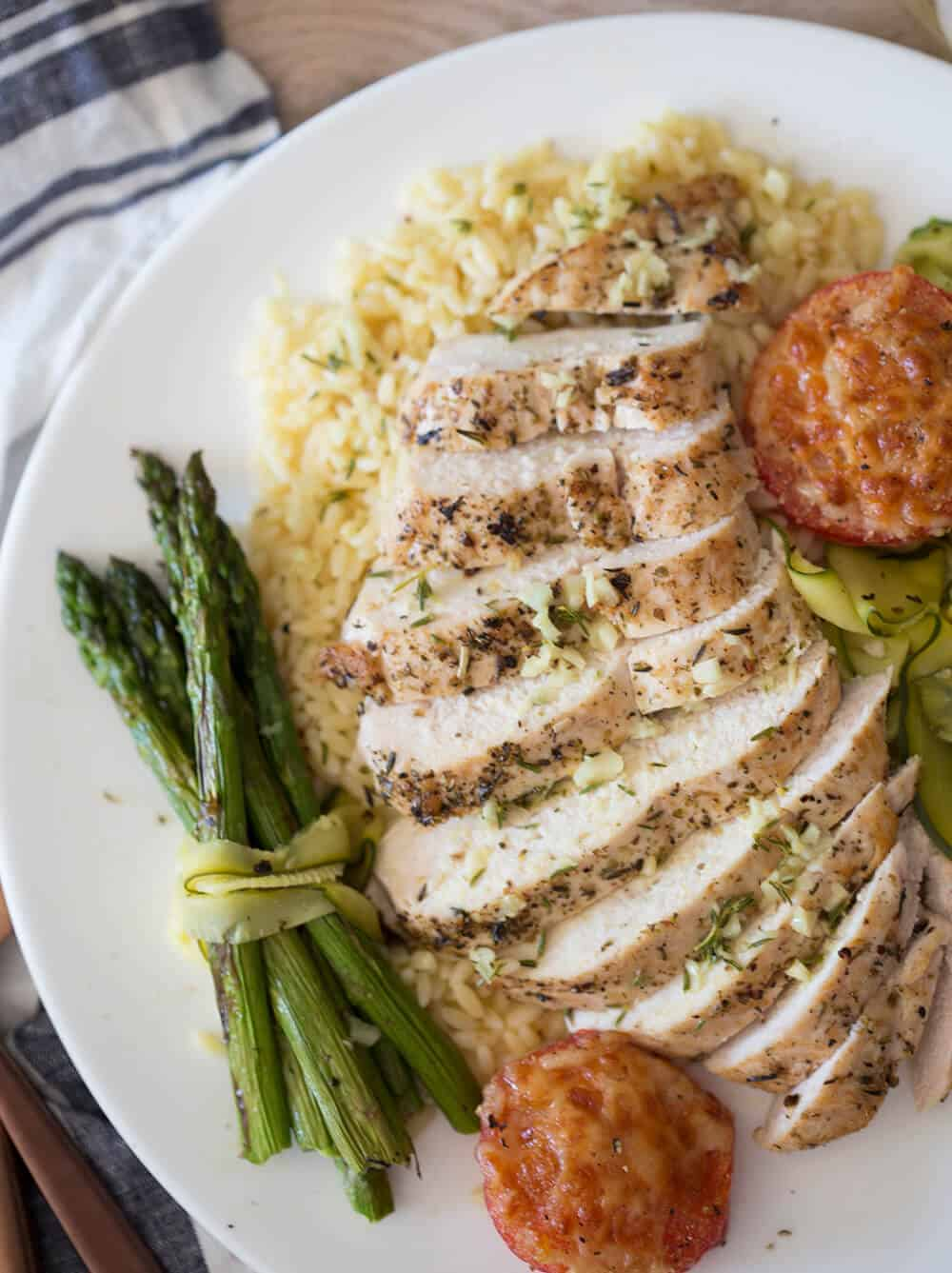 Chicken breast with garlic wine sauce on a plate with rice and asparagus.