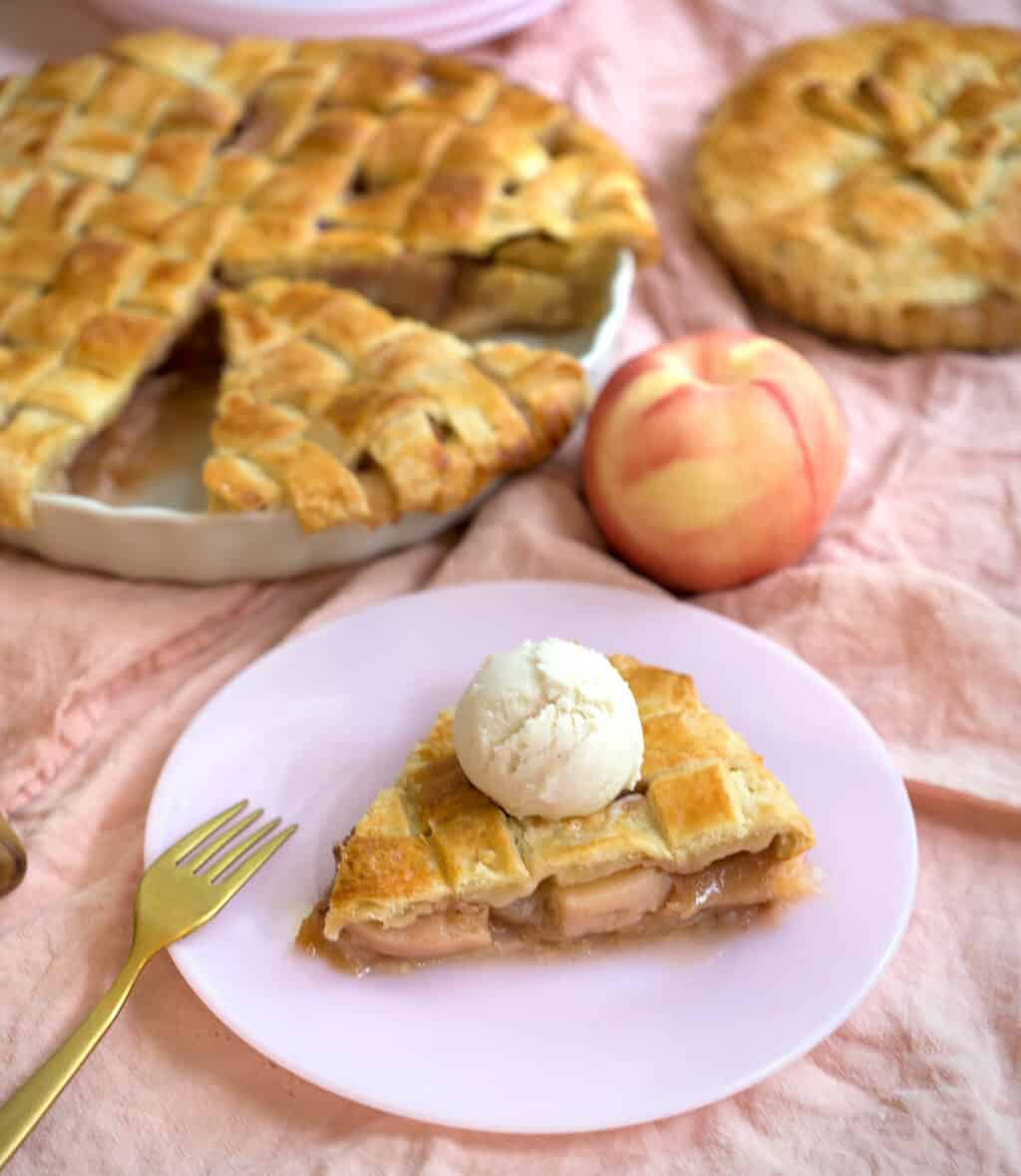 A photo of a piece of peach pie on a plate topped with a scoop of ice cream.