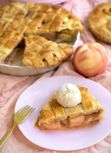 A piece of peach pie with a scoop of vanilla ice cream on top next to two pies