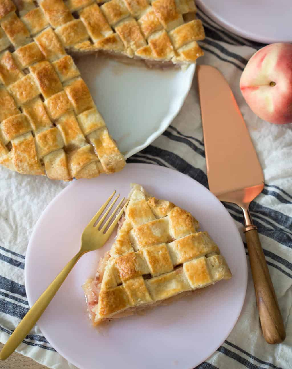 A slice of peach pie on a plate ready to eat.