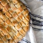 A photo of a peach pie covered in a beautiful woven pie crust.
