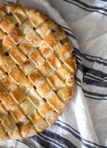 A photo of a peach pie covered in a beautiful woven pie crust.