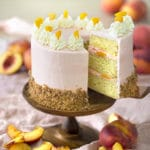 Photo of a peach cake with a piece being removed