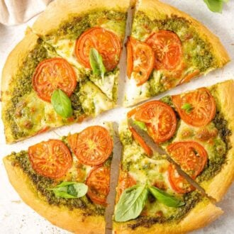 An overhead shot of a pesto pizza cut into slices