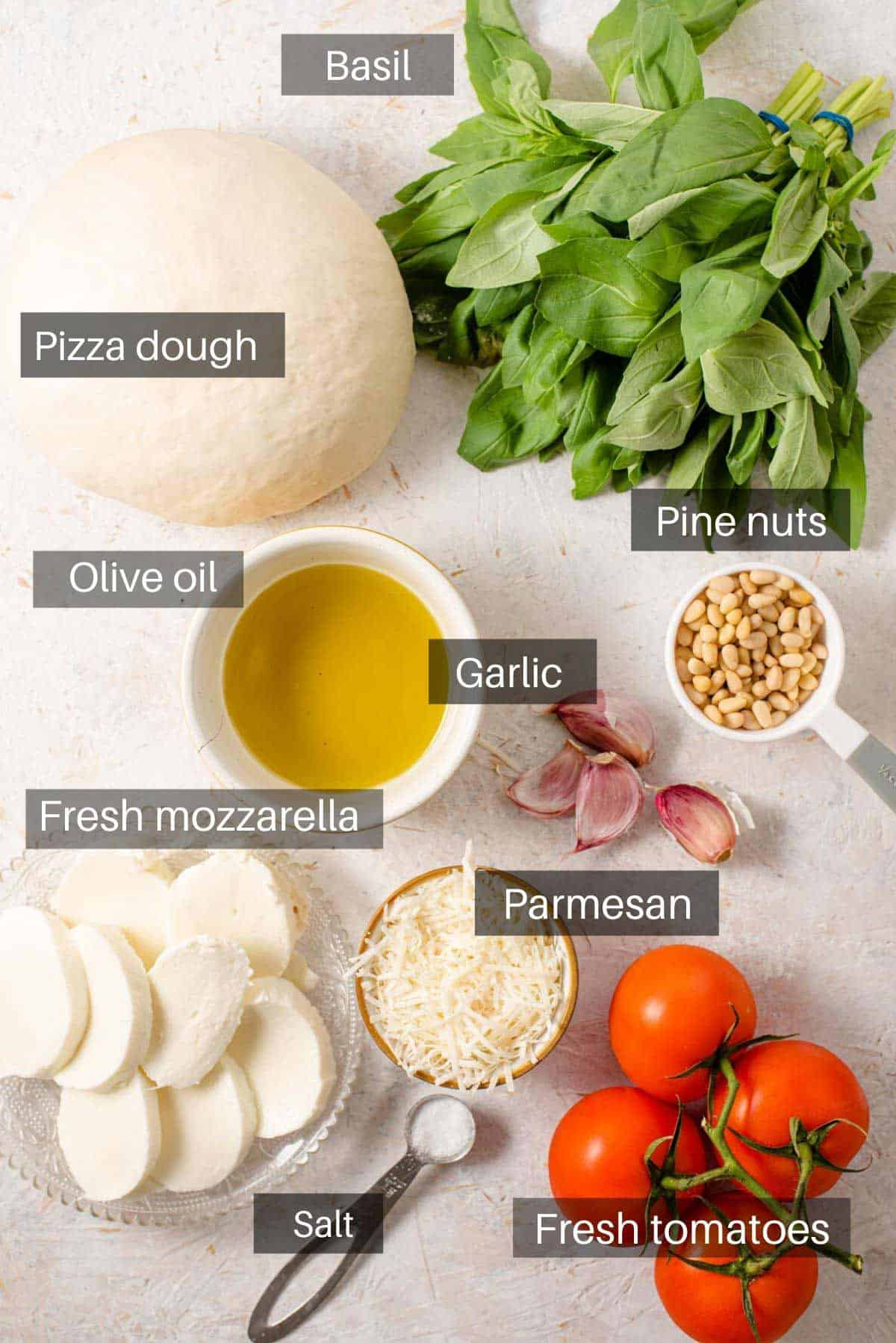 An overhead shot of all the ingredients you need to make a pesto pizza