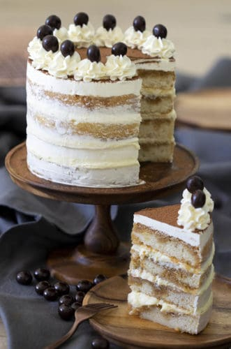 A tiramiisu cake on a wooden cake stand with a piece in the foreground.