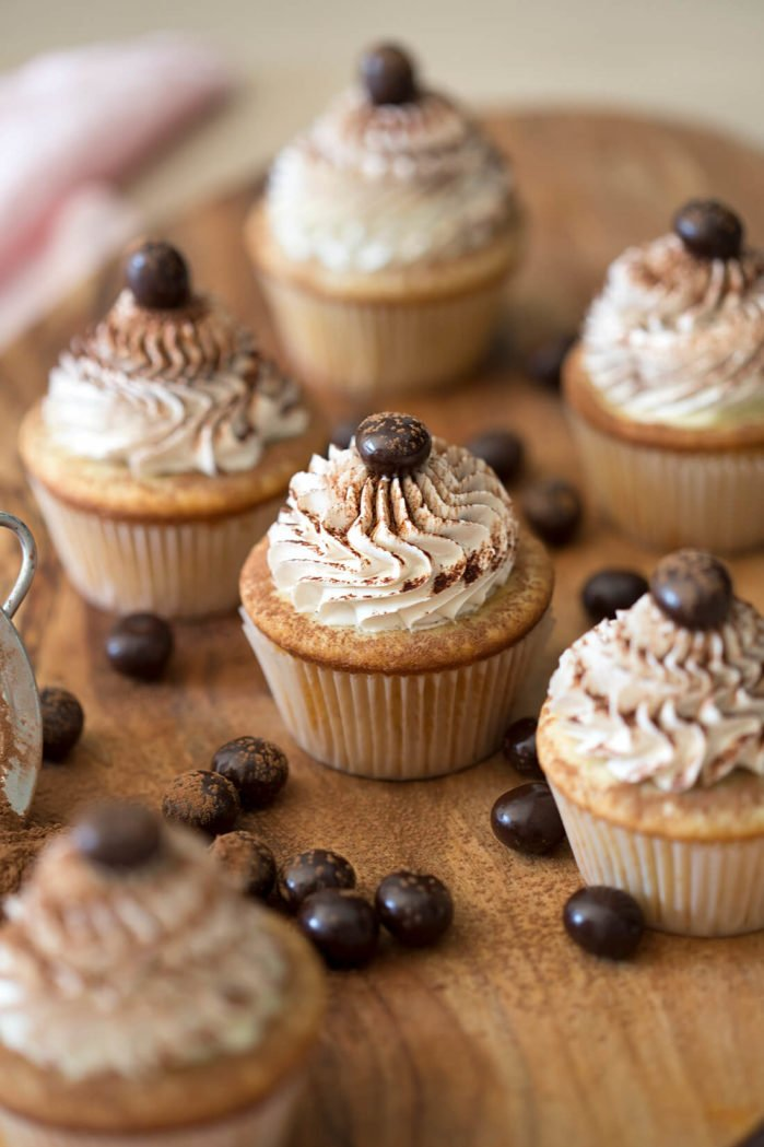 A photo of tiramisu cupcakes on a wooden board