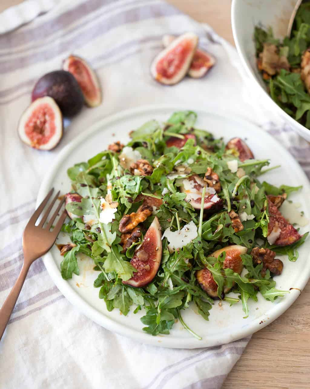 A photo of a fig and walnut salad on a plate ready to be served.