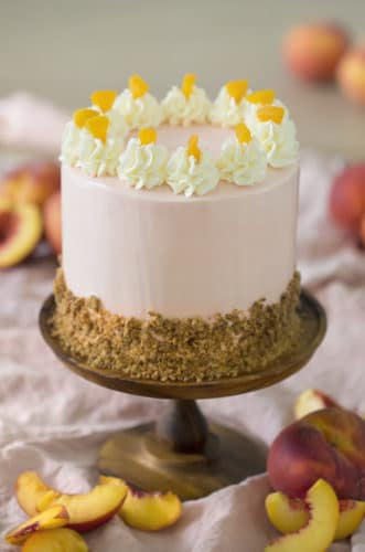 A photo of a peach cake on a wooden cake stand surrounded by peach slices.
