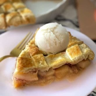 A piece of peach pie with a scoop of vanilla ice cream on top