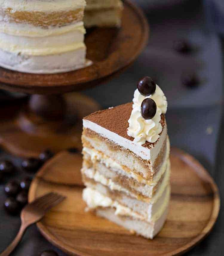 A piece of tiramisu cake on a wooden plate