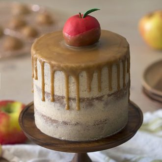 A caramel apple cake on a wooden cake plate.