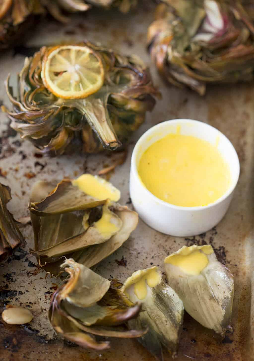 A photo of roasted artichokes with dipping sauce on the side.