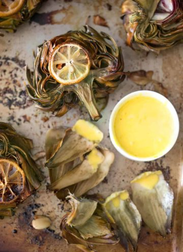 A photo of a Roasted Artichoke with dipping sauce on the side.
