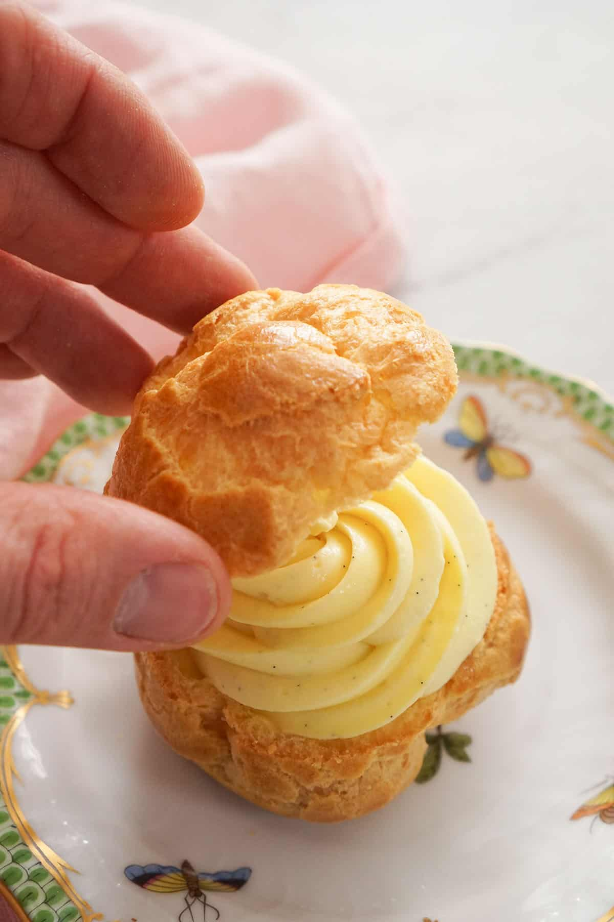 A cream puff getting assembled with piped pastry cream.
