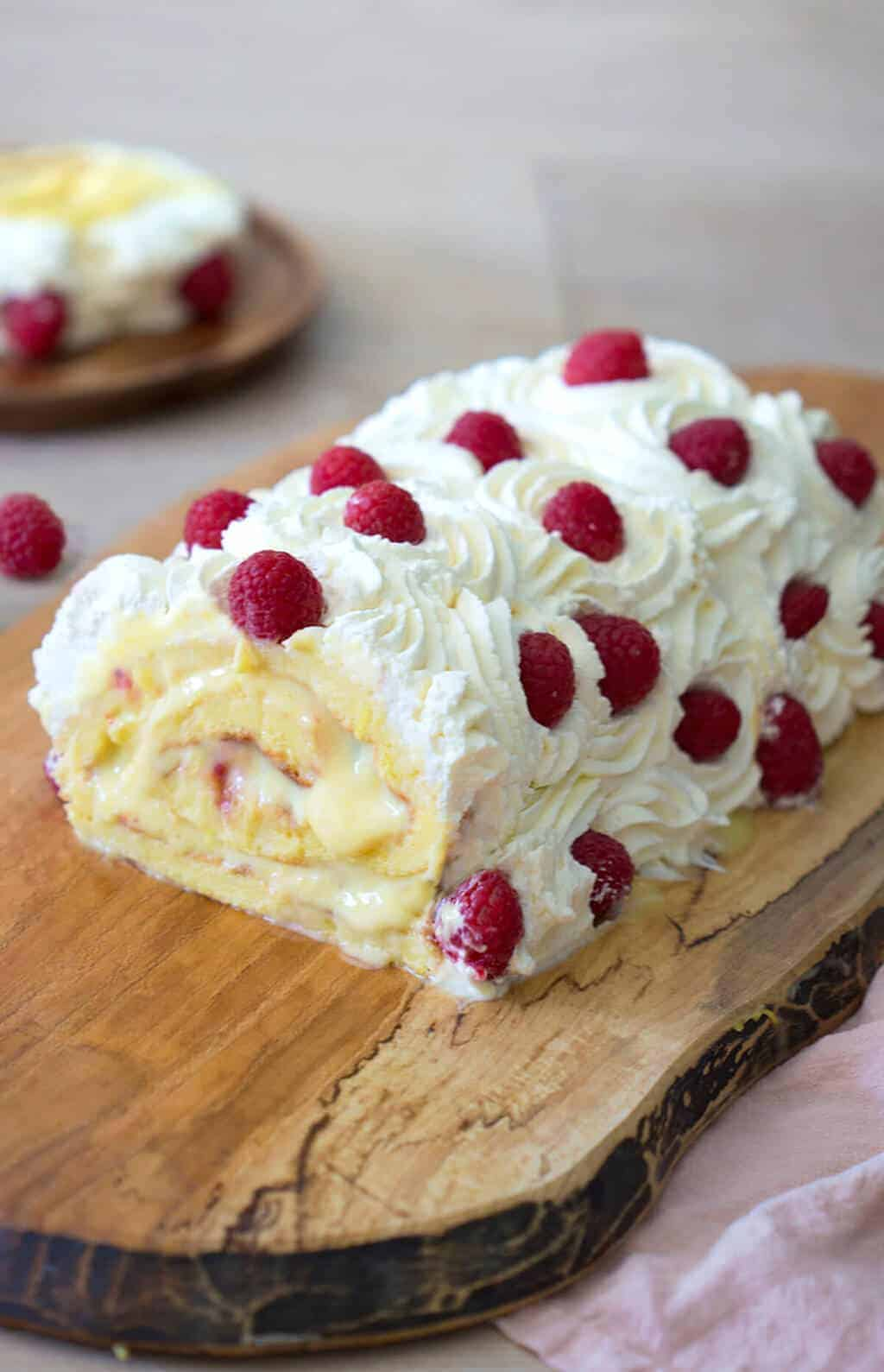 A photo of a Lemon Roll Cake with whipped cream and raspberries on top.