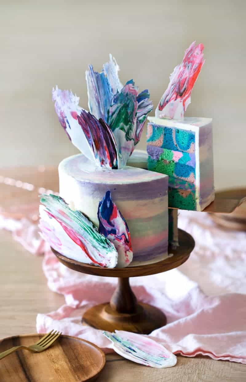 photo of a rainbow Cake on a wooden cake stand