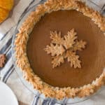 A photo of pumpkin pie with leaves made out of pie crust decorated on top.