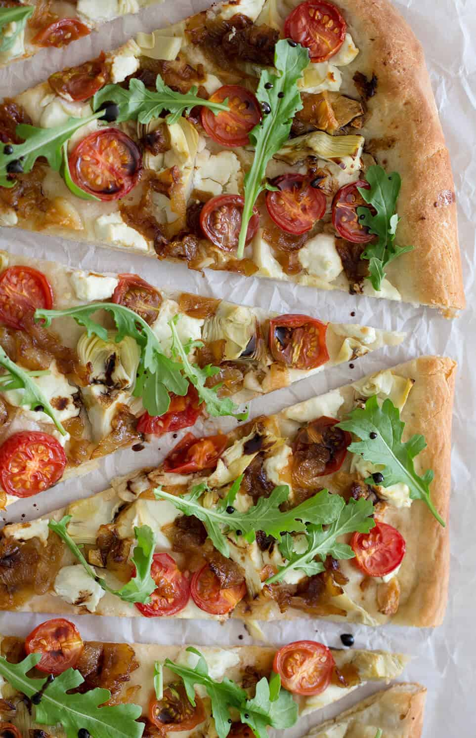 Slices of a homemade artichoke pizza with cherry tomatoes and arugula on top.