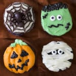 photo showing four different halloween cupcakes, mummy, frankenstein, jack o'lanterns and a spider on a web.