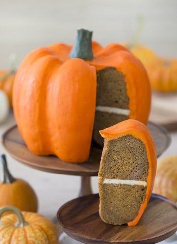 Photo of a large orange pumpkin cake with a piece in the foreground.