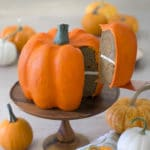 photo of a pumpkin shaped cake on a wooden stand with a piece being removed.