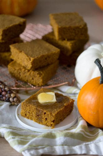 A photo of pumpkin cornbread on a plate with butter on top.