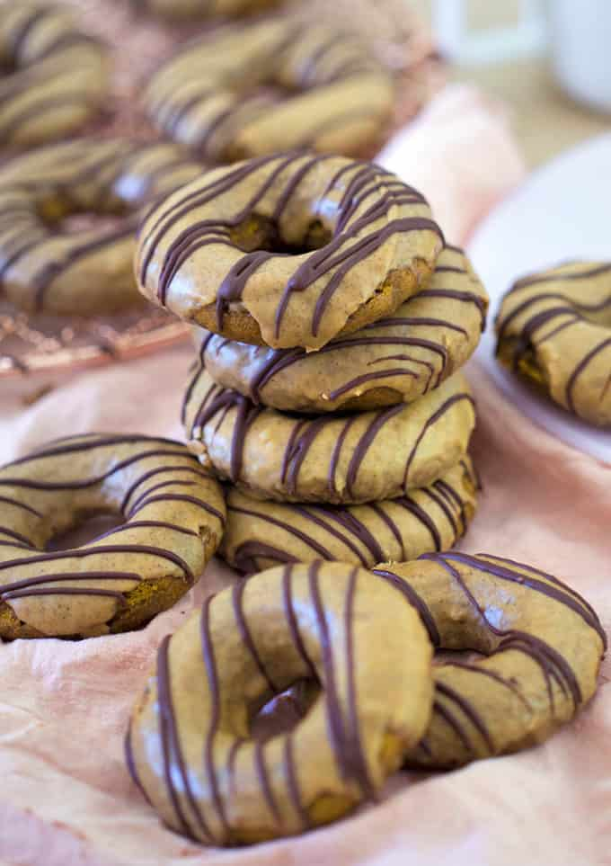 A stack of pumpkin donuts with chocolate streaks on a pink linen