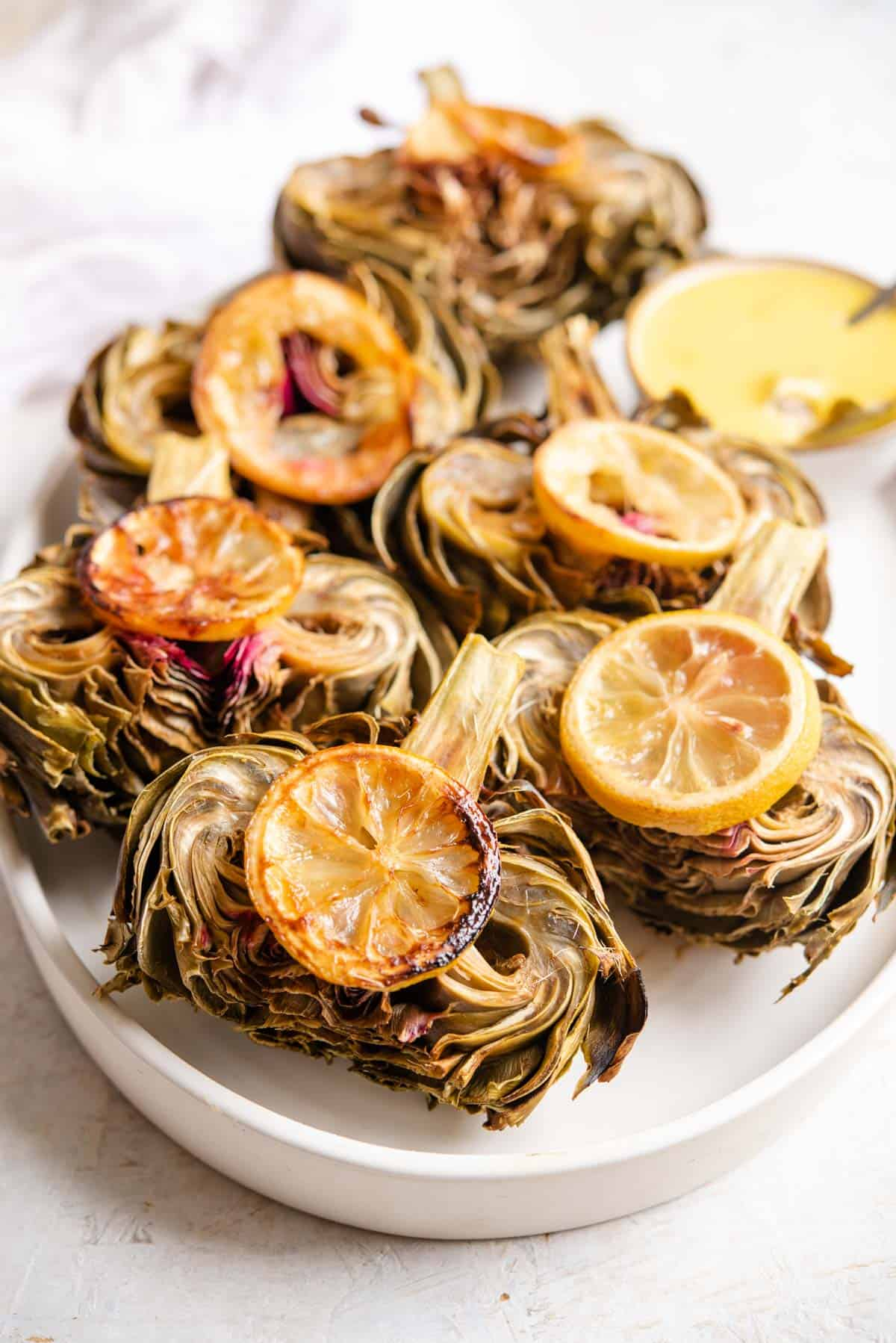 A side shot of roasted artichokes on a serving plate