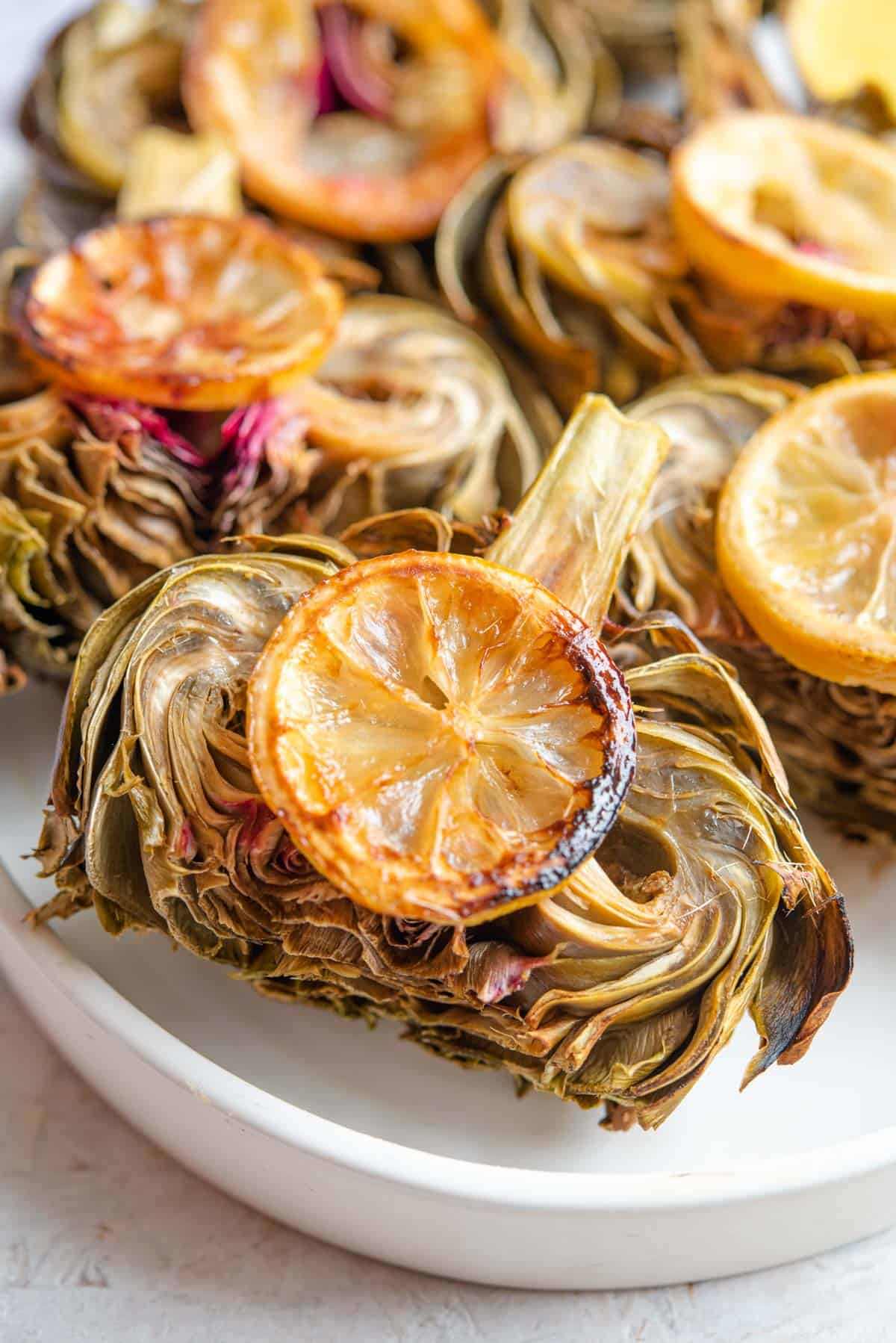 A close up of a roasted artichoke on a plate