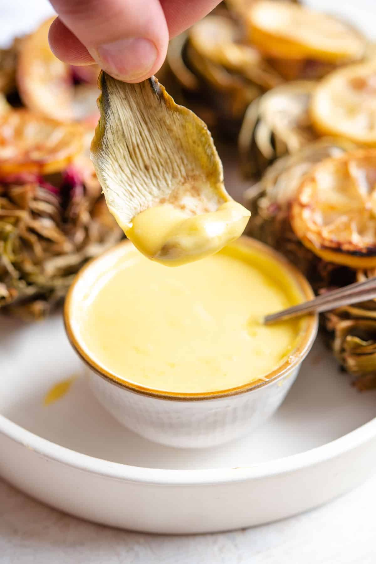 A close up of dipping an artichoke leave into aioli