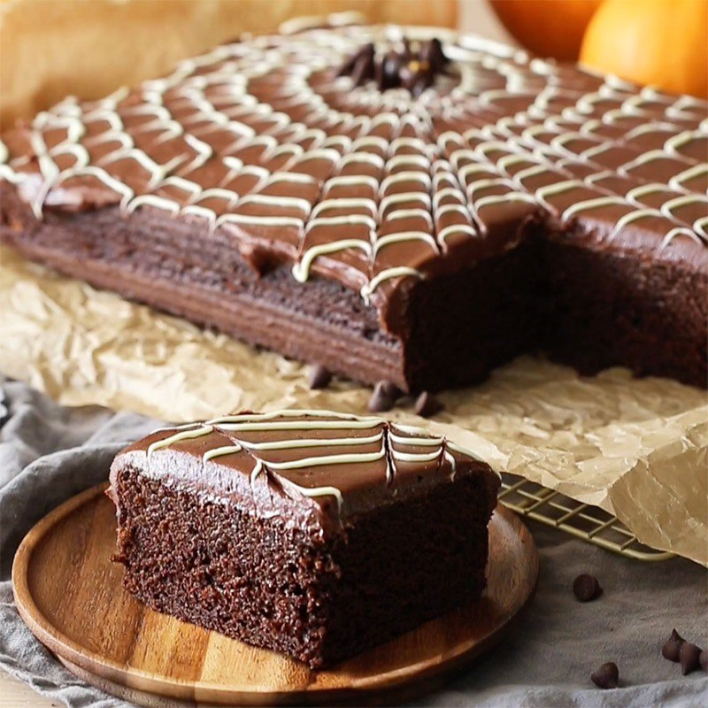 a photo of a spider web sheet cake with a bpiece in teh foreground on a wooden plate.