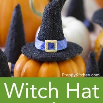 various black witch hat cookies on top of mini pumpkins
