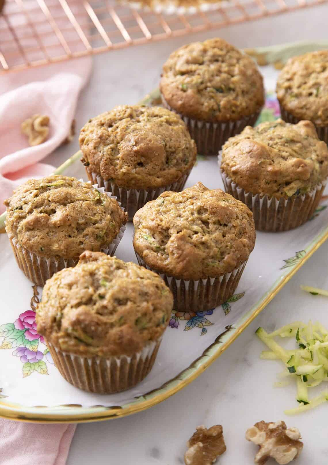 Zucchini muffins with toasted walnuts on a serving tray.