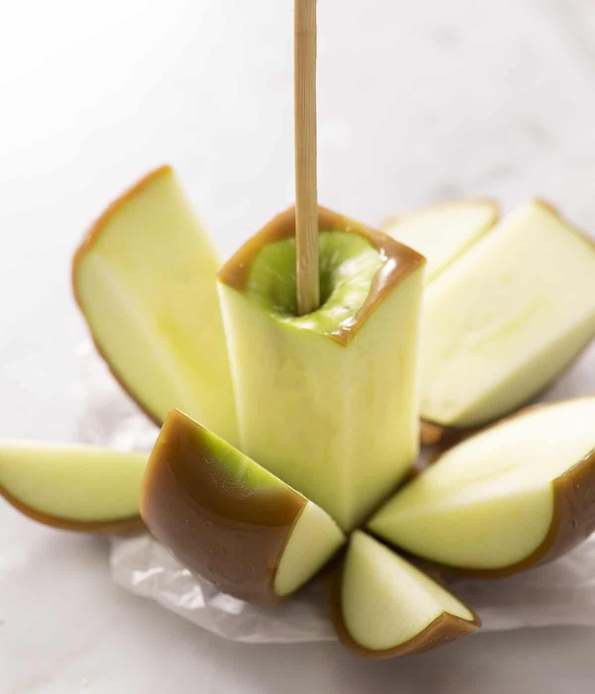 A caramel apple cut into pieces.